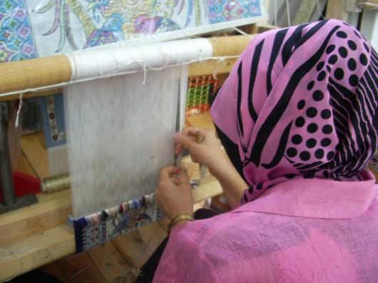 Mujer Turca tejiendo una alfombra de seda